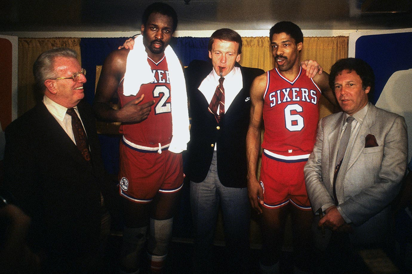 Moses Malone and Dr. J pose with 76ers coach Billy Cunningham, alongside NBA commissioner Larry O'Brien (left) and Sixers owner Harold Katz (right) in the locker room after sweeping the Los Angeles Lakers in the 1983 NBA Finals.