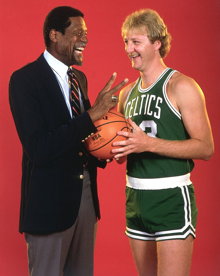 Bill Russell and Larry Bird, two of the all-time best NBA players, talk with each other. The pair is a big reason Boston has more NBA championships than any other franchise.