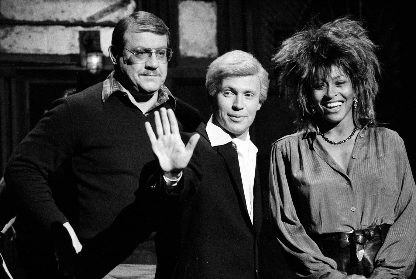 "Host Alex Karras stands with Billy Crystal, in character as ""Fernando,"" and musical guest Tina Turner during a rehearsal for Saturday Night Live on Jan. 31, 1985 in New York City."