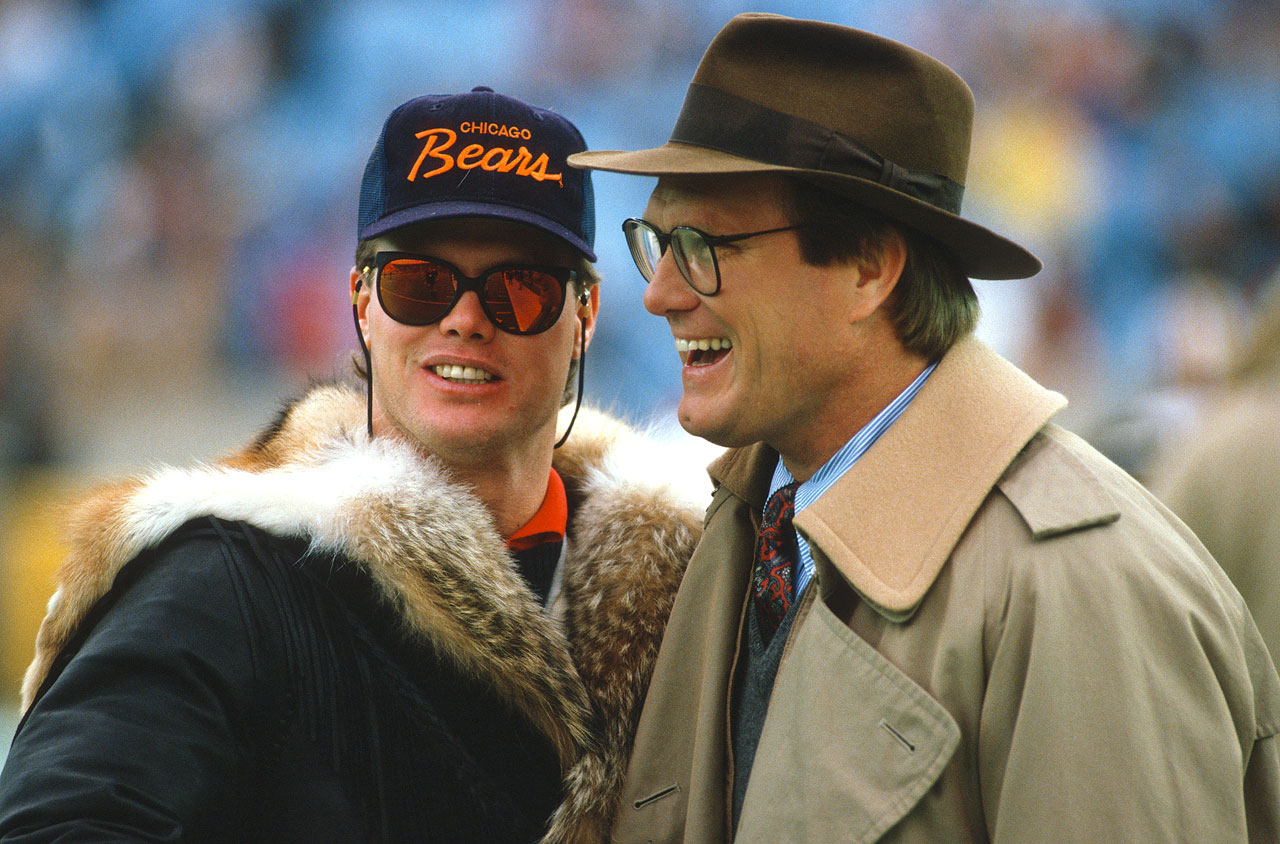 Bears quarterback Jim McMahon laughes with CBS football analyst Terry Bradshaw from the sidelines.