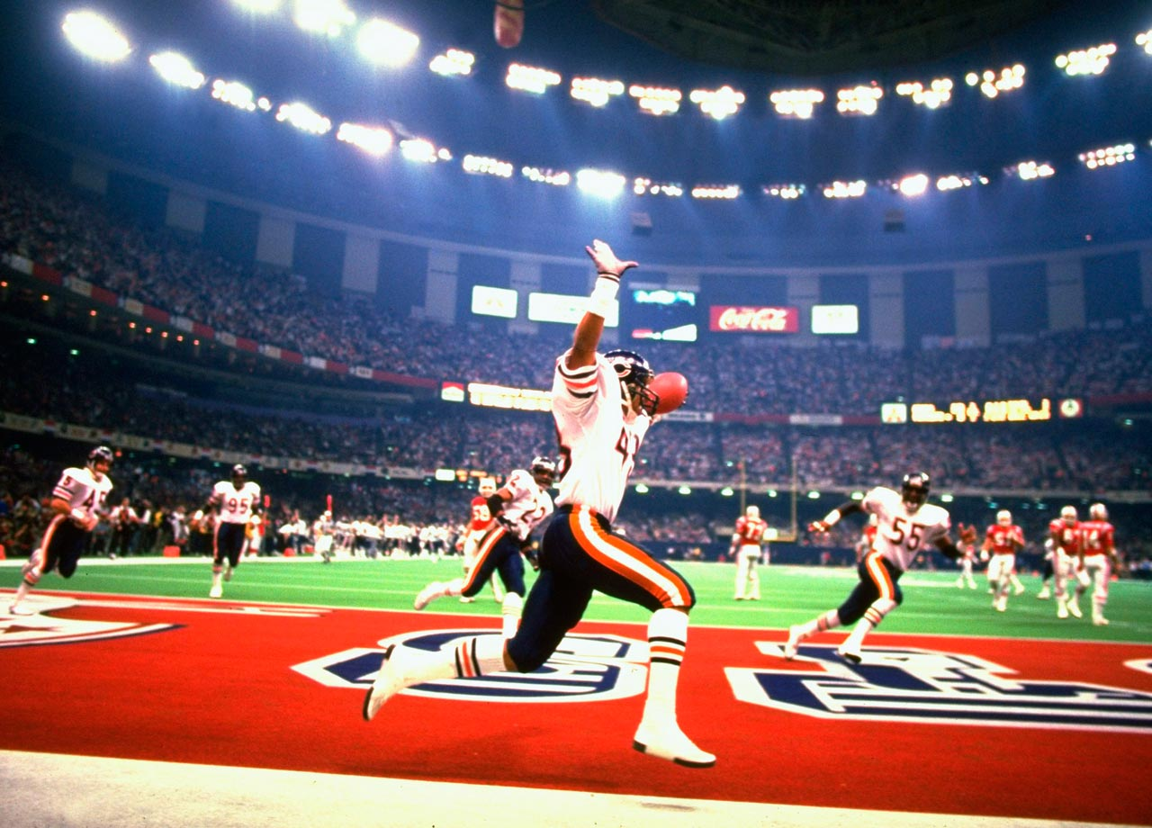Chicago Bears defensive back Reggie Phillips raises his arms after returning an interception 28 yards for a touchdown against the New England Patriots. The Bears' innovative 46 defense dominated the game, registering seven sacks and allowing just seven rushing yards in the 46-10 win, while directly putting nine points on the board.