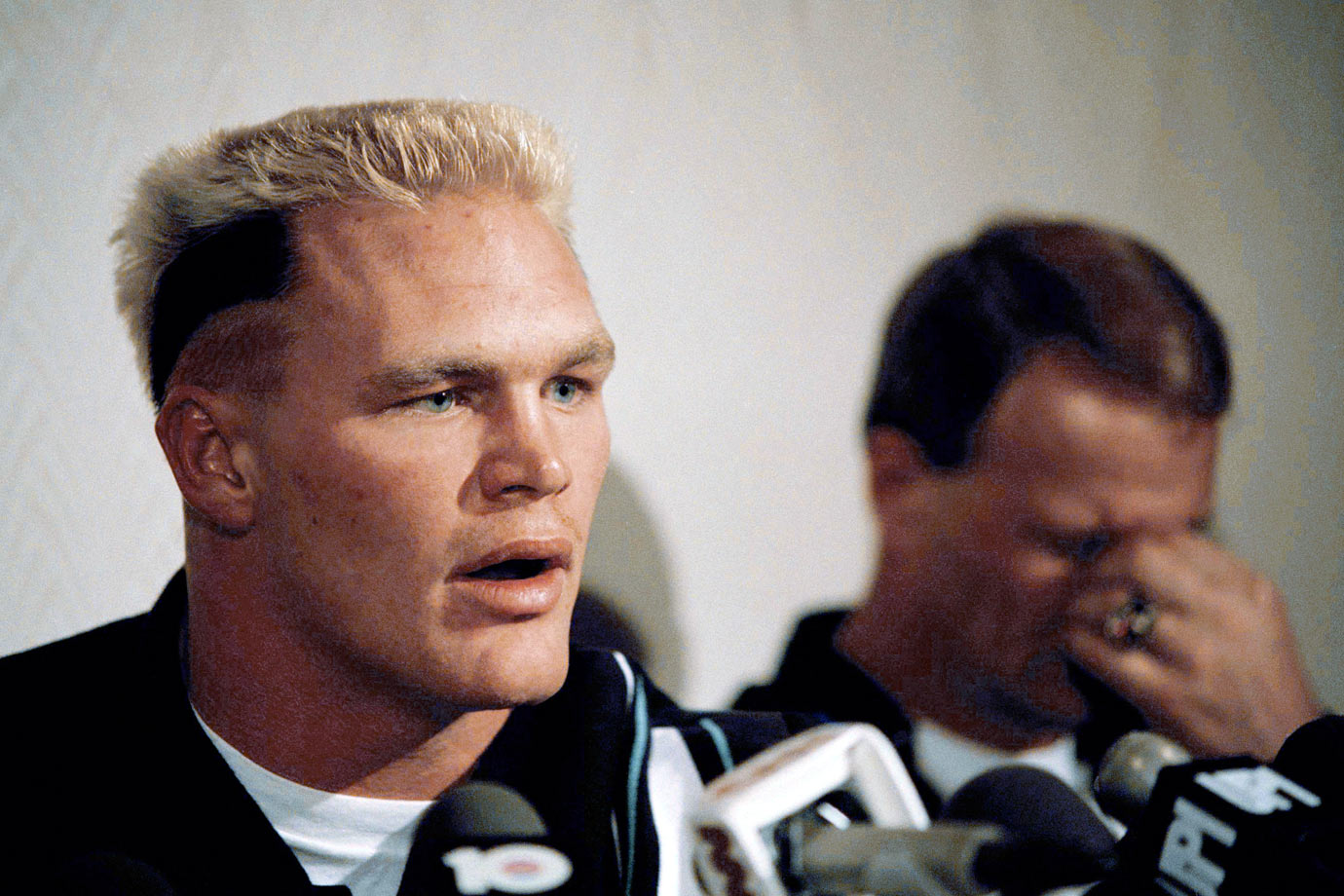 With Oklahoma head coach Barry Switzer reacting in the background, Brian Bosworth speaks to the press about his being barred from playing in the Orange Bowl on New Years Day.