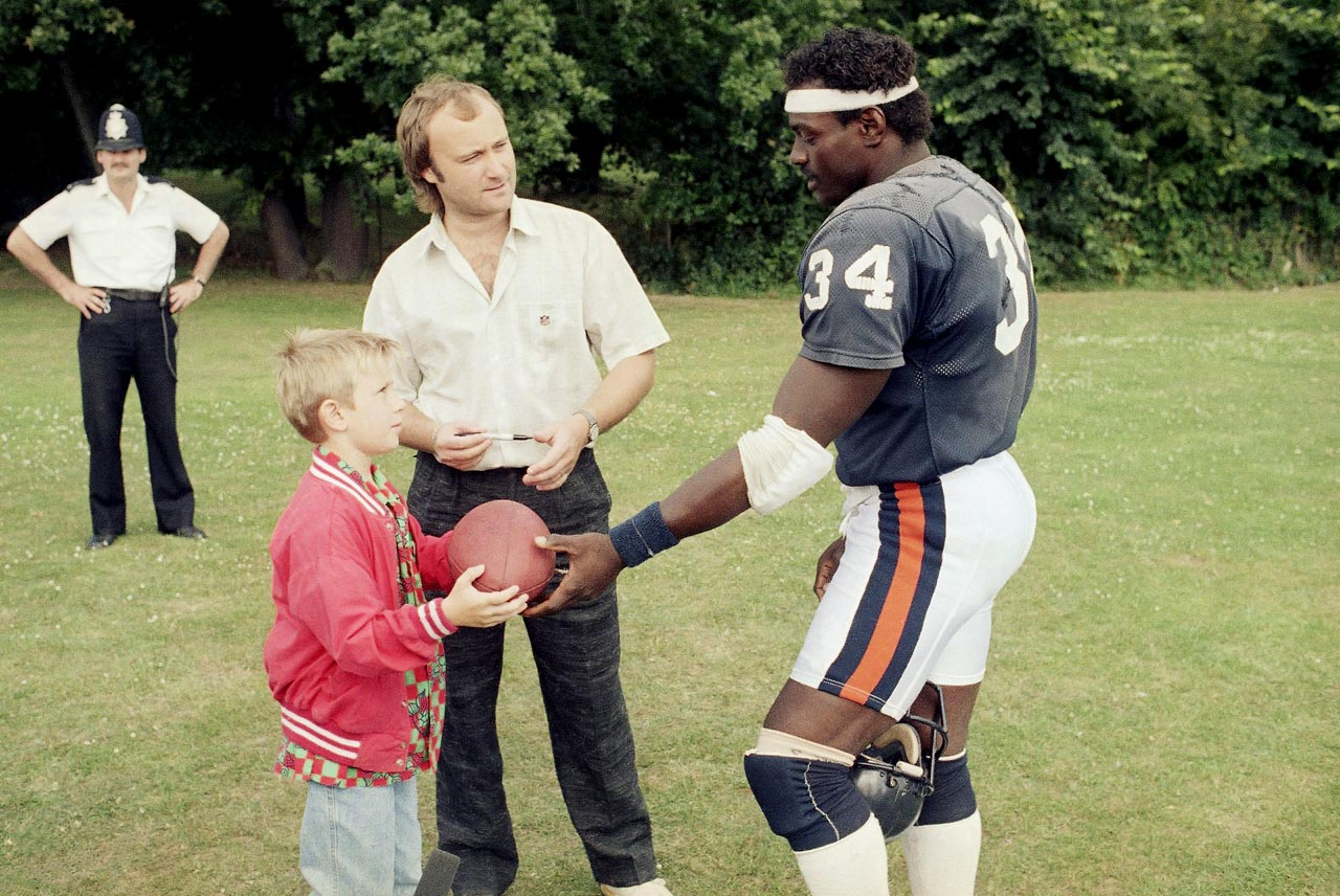 "Even singer Phil Collins wanted some ""Sweetness"" memorabilia. Collins, with his son Simon, receives an autograph from Payton before the 1986 Bears-Cowboys regular season contest dubbed the ""American Bowl."""