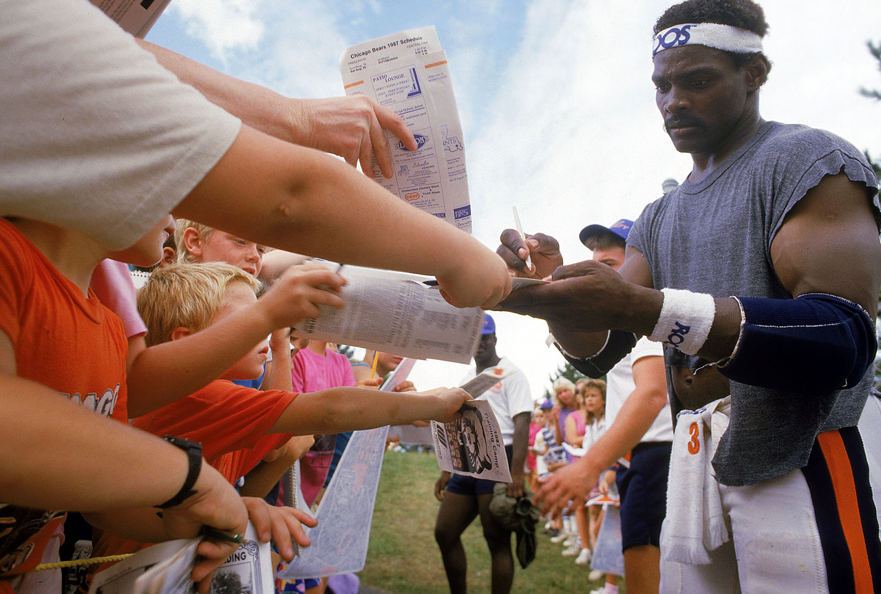 The popular Walter Payton signs autographs during training camp.