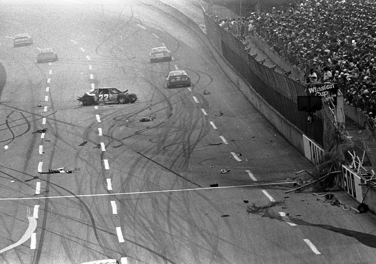 This is the 10-car crash that was the impetus for restrictor plates. Allison blew his right rear tire, spun on the frontstretch and then flew up into the catch fence, tearing up a large section. After taking out 150 feet of fencing and nine heavy support posts, Allison's car spins back onto the track. The race was red flagged for 2 hours 38 minutes and 14 seconds. Allison is not hurt.