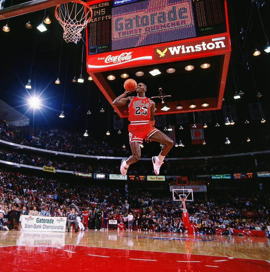 Michael Jordan leaps from the free-throw line for a perfect-score dunk in the 1988 NBA Slam Dunk Contest. A prolific dunker throughout his career due to his tremendous leaping ability, Jordan won back-to-back dunk contests in 1987 and '88.