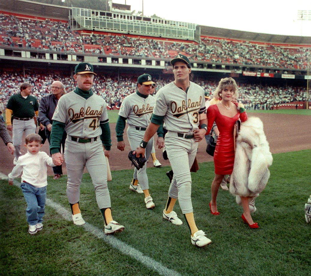 Ken Phelps of the Oakland A's walks with his son Nathan alongside teammate Jose Canseco and his wife Ester as they leave the field at Candlestick Park.