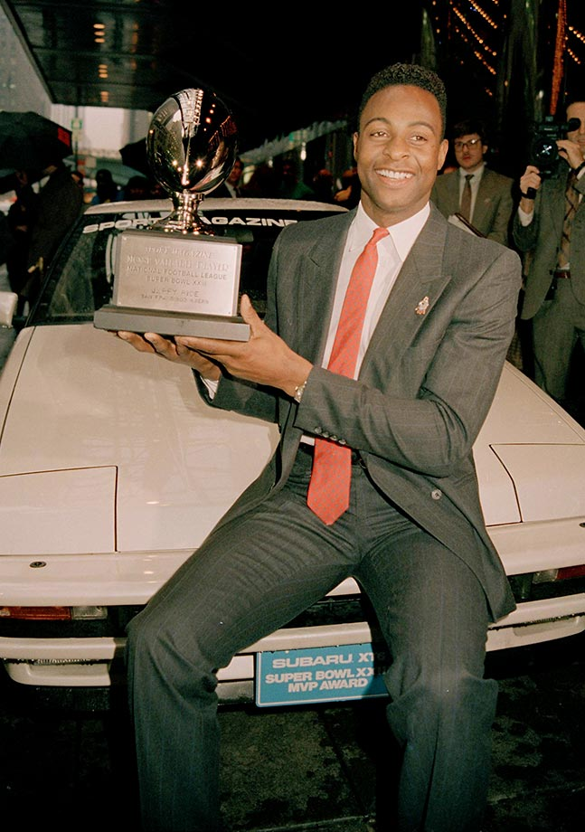 Jerry Rice of the San Francisco 49ers sits on the hood of his new car holding his Most Valuable Player trophy in New York City.