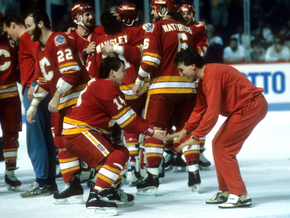 """Calgary's pot-stirring little big man Theoren Fleury (left), who stood at 5'-6"""", concluded his rookie season with the Cup and a happy low-five shared with teammate Tim Hunter after the Flames dispatched the Canadiens in Game 6 at the Montreal Forum."""