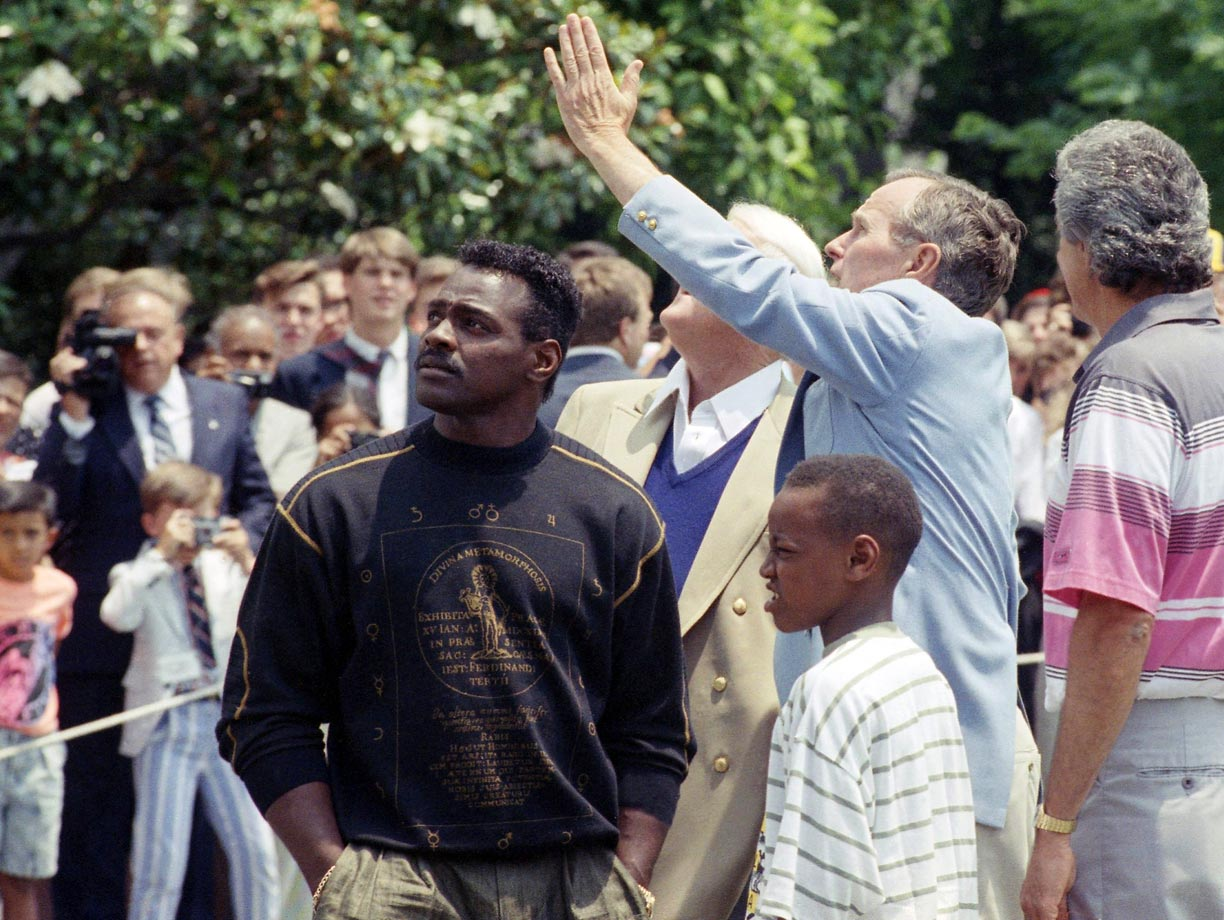 U.S. President George H.W. Bush points out White House renovations to his guests, including Walter Payton and his son Jarrett on June 22, 1990 in Washington, D.C.