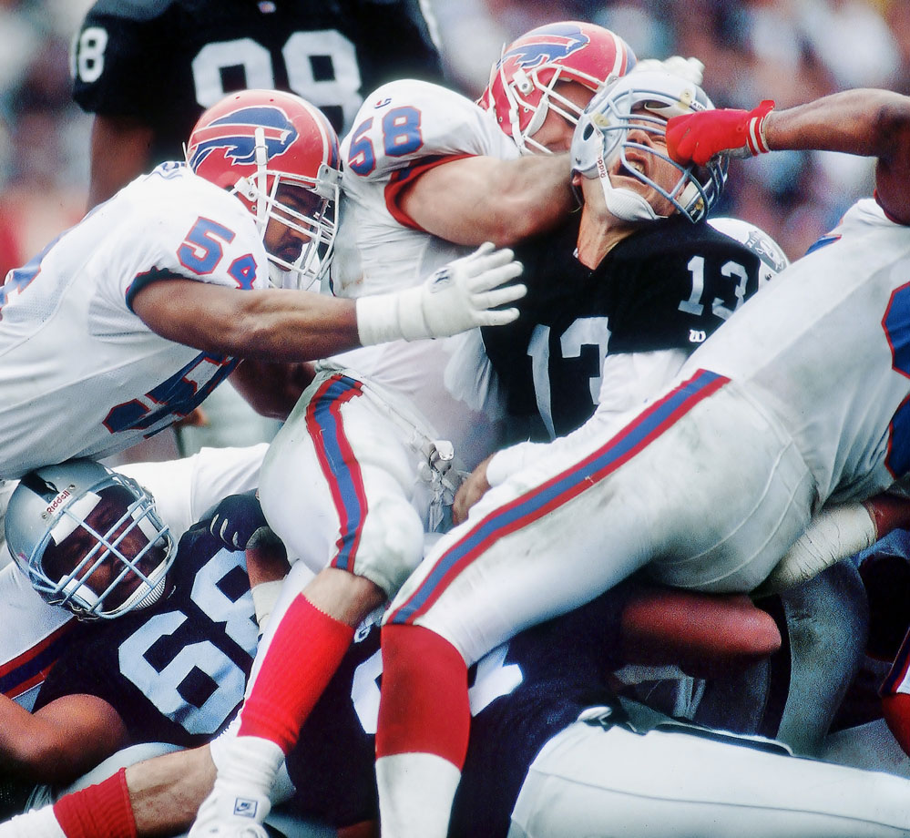 Raiders quarterback Jay Schroeder was an unlucky 13 when Bills defenders put a new twist on the old gang tackle.