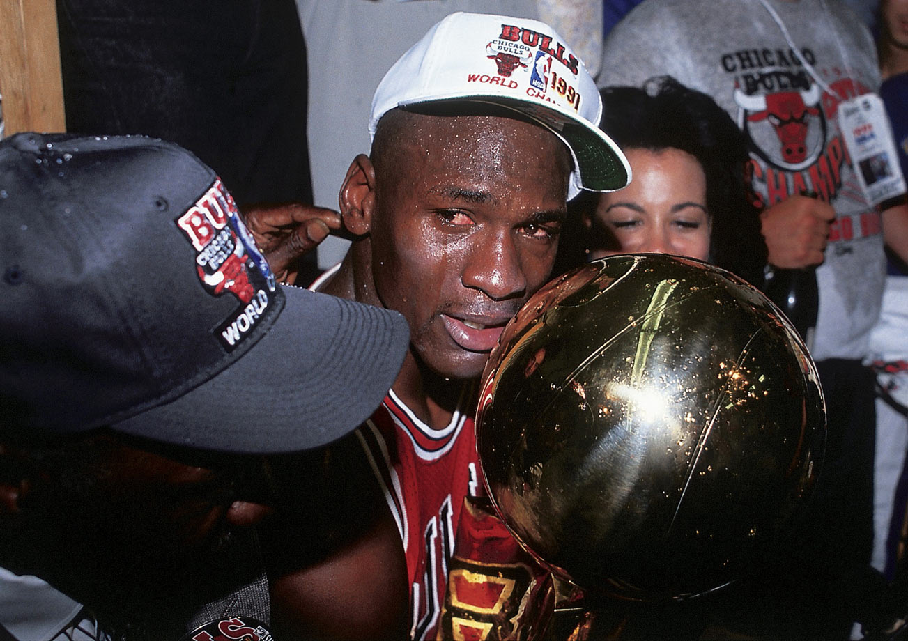 Michael Jordan smiles after bringing home the first NBA title of his career in 1991. After losing to the Detroit Pistons in the Eastern Conference Finals the two years prior, the Bulls swept Detroit and then defeated the Lakers in five games for the first championship in franchise history. He cried after receiving the trophy.