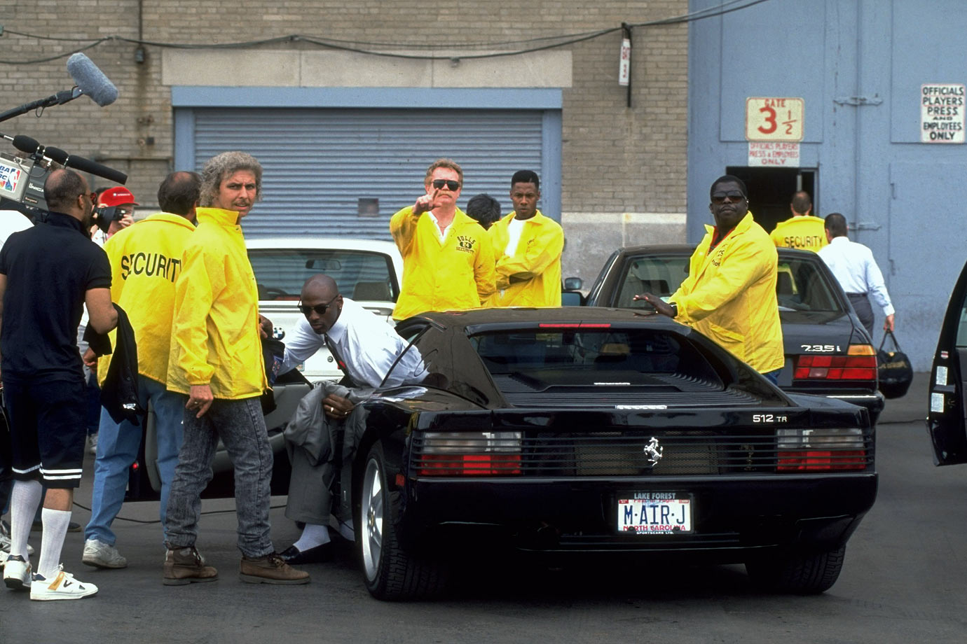 Security guards crowd around Michael Jordan as he gets out of his Ferrari to enter Chicago Stadium in May 1992.