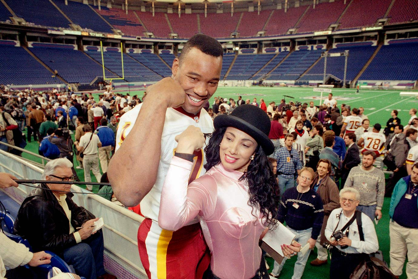 Redskins defensive end Charles Mann compares muscles with MTV's Julie Brown at Super Bowl XXVI Media Day in Minneapolis.