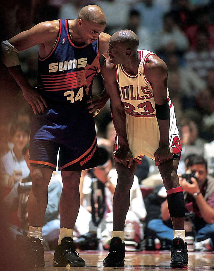 Taking a break from the action of the 1993 NBA Finals, Michael Jordan and Charles Barkley chat in Game 5. Jordan averaged an NBA Finals-record 41 points in the series, becoming the first player to win three straight Finals MVPs.