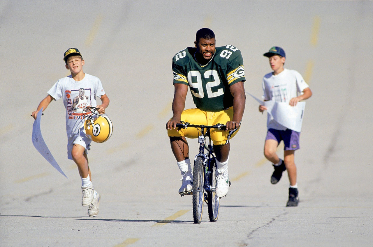 Green Bay Packers DE Reggie White rides a bicycle to training camp at St. Norbert College as fans follow on July 19, 1993 in De Pere, Wis.