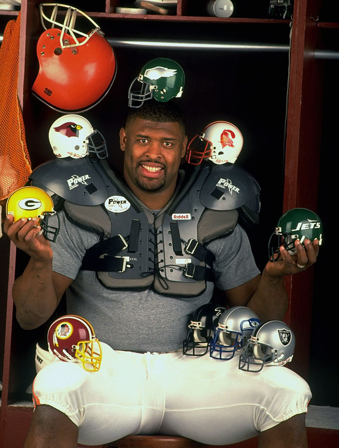 Free agent DE Reggie White poses with multiple NFL team mini-helmets on March 6, 1993 in the locker room at the Browns Training Facility in Berea, Ohio.