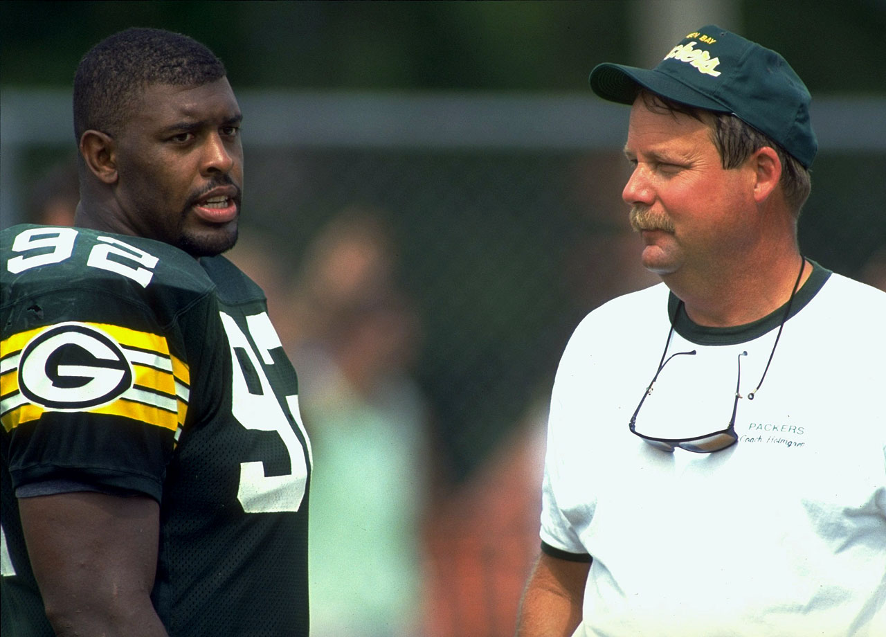 Green Bay Packers DE Reggie White talks with head coach Mike Holmgren during training camp on July 22, 1993 in La Crosse, Wis.