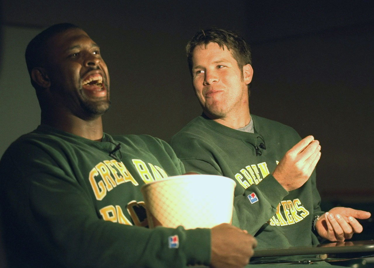 Favre and teammate Reggie White enjoy some popcorn while giving an interview.