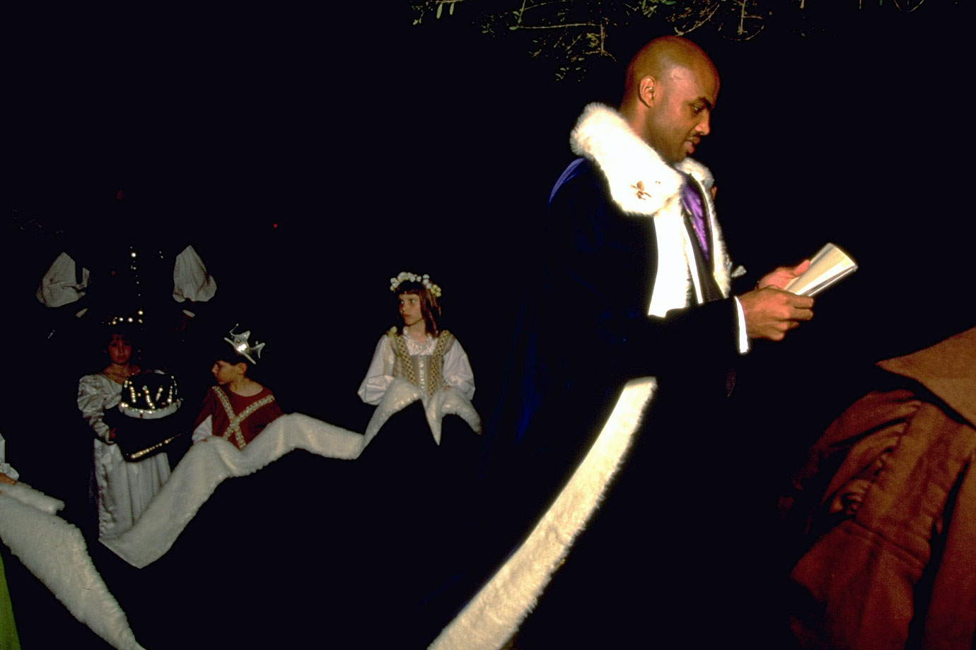 Charles Barkley dresses in royal regalia with children holding his cape at a charity fundraiser.