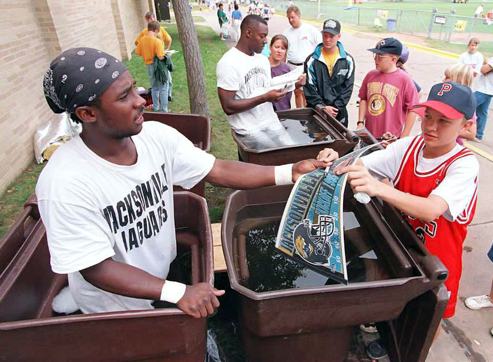 Former Heisman Trophy winner Desmond Howard (left) and teammate Willie Jackson sign autographs while standing in trash cans filled with ice water during training camp for the expansion Jaguars at the University of Wisconsin-Stevens Point campus.