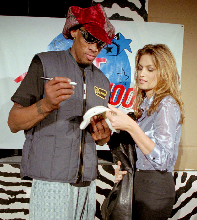 "Rodman, then a guest on MTV's ""House of Style,"" signs a hat for supermodel and host Cindy Crawford."