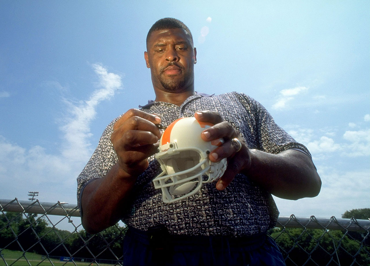 Green Bay Packers DE and Tennessee Volunteers alum Reggie White autographs a mini-helmet at Reggie and Raleigh McKenzie football camp on June 20, 1996 in Knoxville, Tenn.