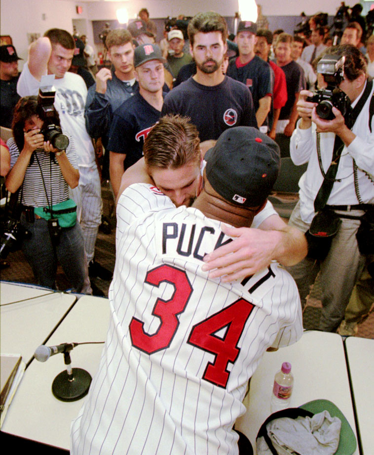 Kirby Puckett gets a hug from teammate Chuck Knoblauch as other players wait to wish him well after Puckett announced his retirement from baseball.
