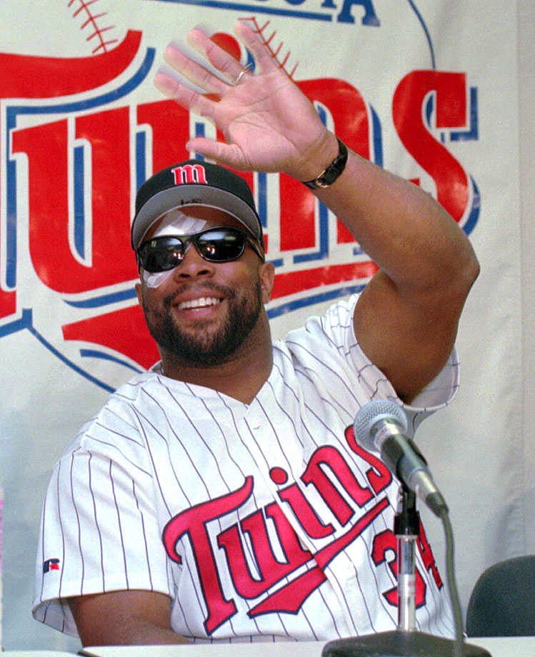 Kirby Puckett waves to teammates during his news conference where he announced his retirement from baseball on July 12, 1996, just hours after undergoing eye surgery which revealed irreversible damage to his retina.