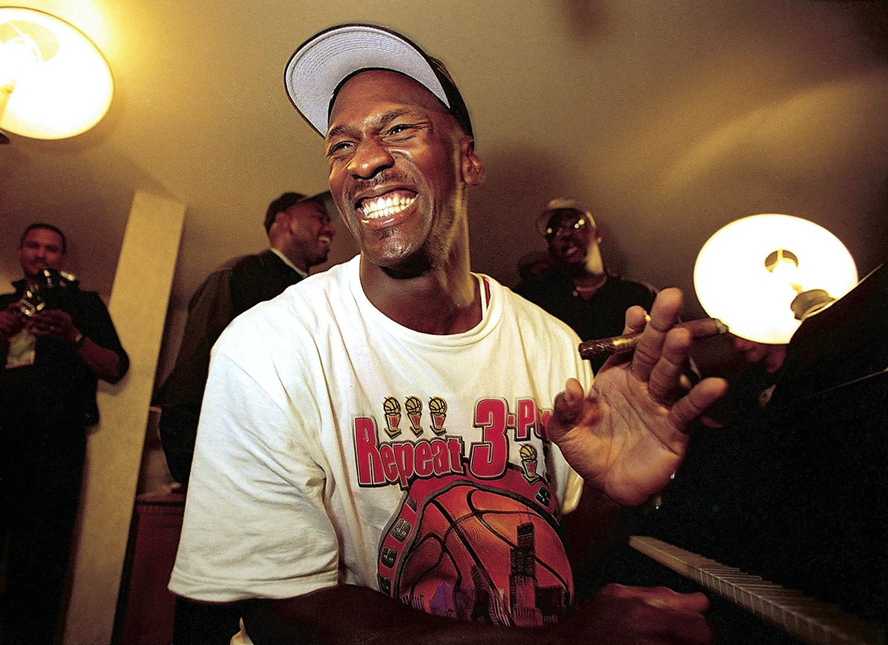 Michael Jordan is all smiles, playing piano and smoking a cigar after winning his sixth national championship in 1998. The title finished off the second three-peat of championships of Jordan's career.
