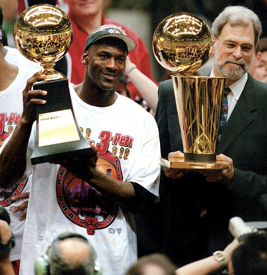 Michael Jordan holds the Finals MVP trophy as Phil Jackson raises the Larry O'Brien Trophy following the Bulls' victory over the Utah Jazz to win the 1998 NBA Finals. Jordan averaged 33.5 points per game in the six-game series to claim the last of his six Finals MVP Awards.