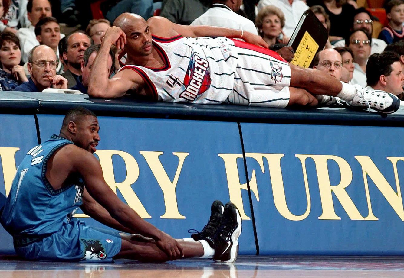 Charles Barkley lays alongside Reggie Jordan during a Rockets-Timberwolves game. Barkley was hampered by injuries in Houston, missing 145 games in four seasons before retiring in 2000.