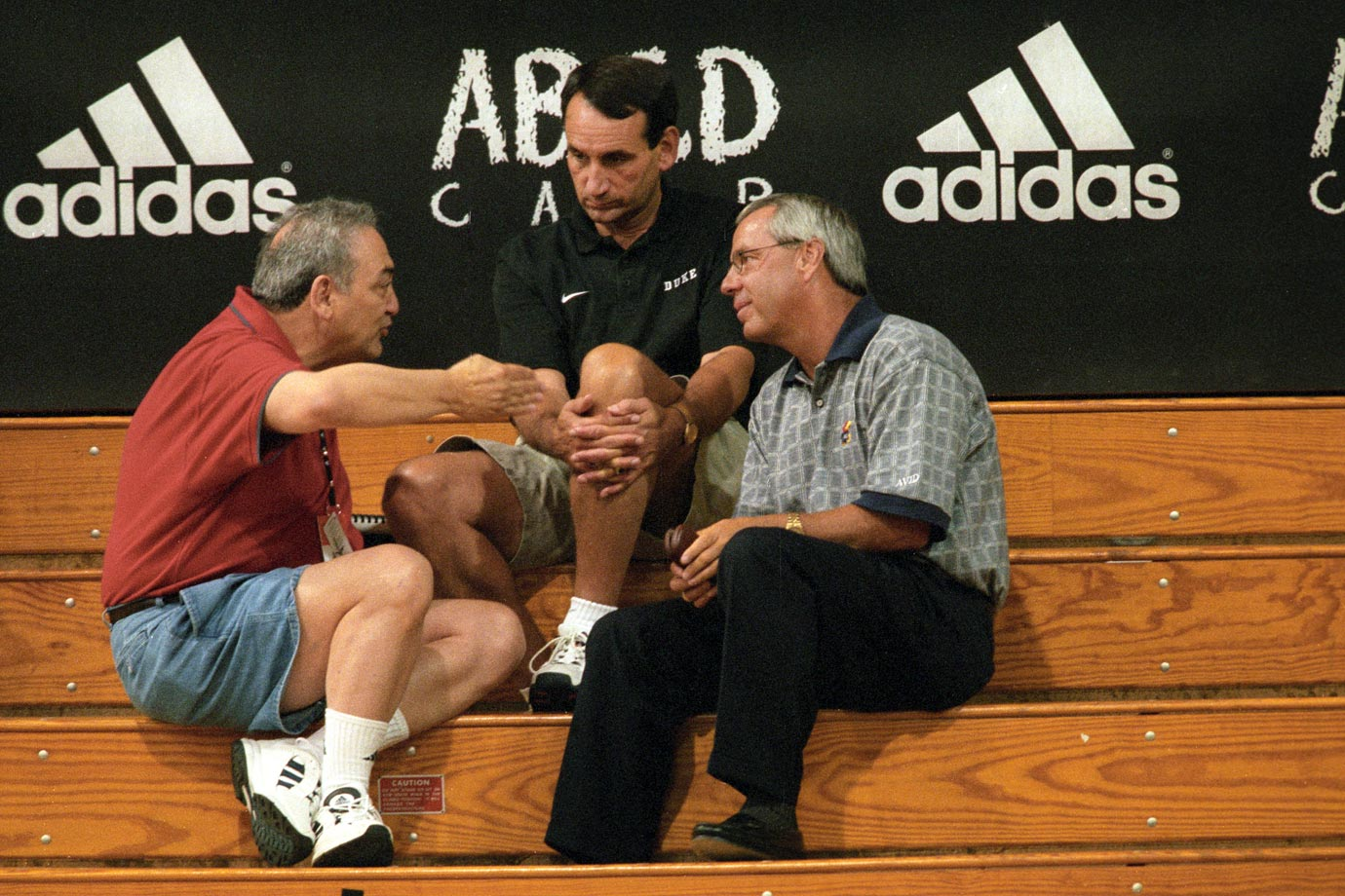 Scout Sonny Vaccaro talks with Duke coach Mike Krzyzewski and Kansas coach Roy Williams during the Adidas ABCD Camp in Teaneck, N.J. in 1998.