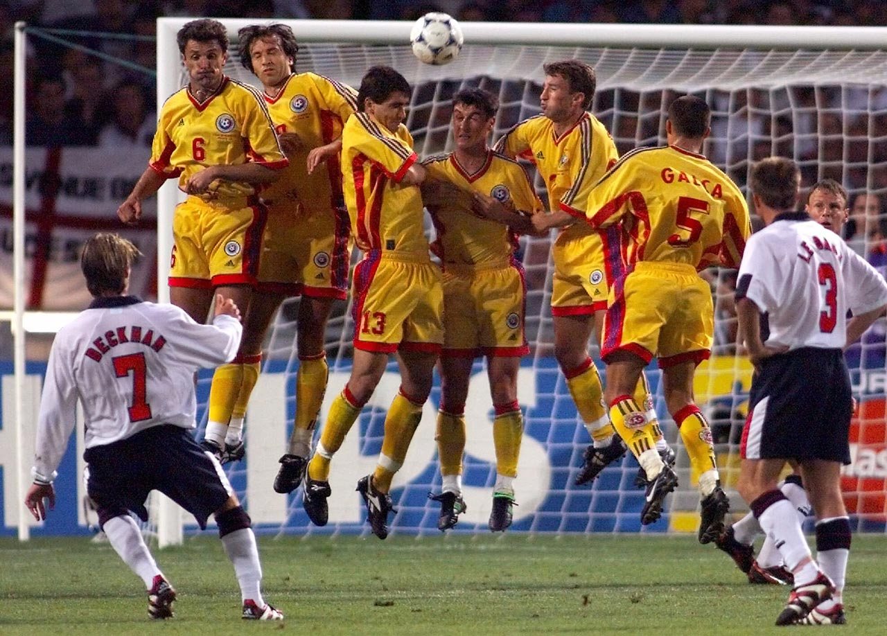 David Beckham's free kick curls over the wall of jumping Romanian defenders during England's Group G match against Romania in the 1998 World Cup.
