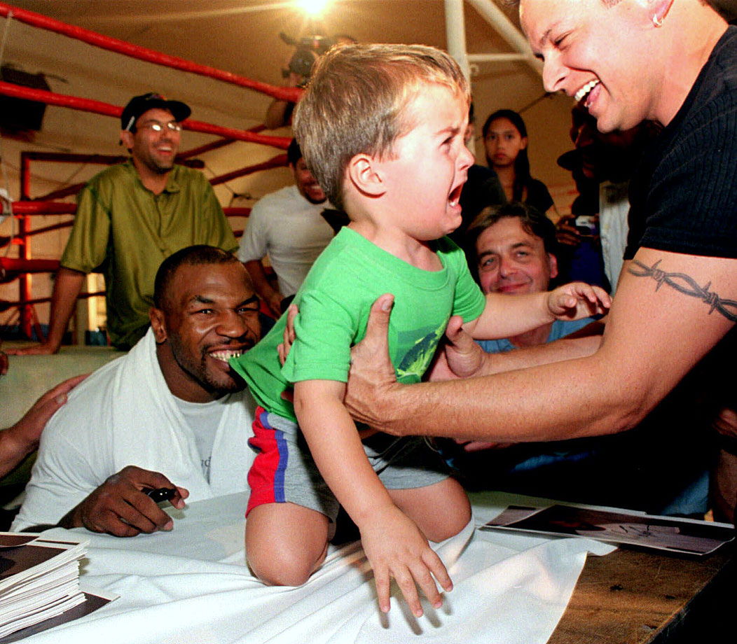 Two-year-old Florin Bouros of Tempe, Ariz., cries as he reaches for his father as boxer Mike Tyson playfully bites at his shirt at a downtown Phoenix gym where people came to see Tyson work out.