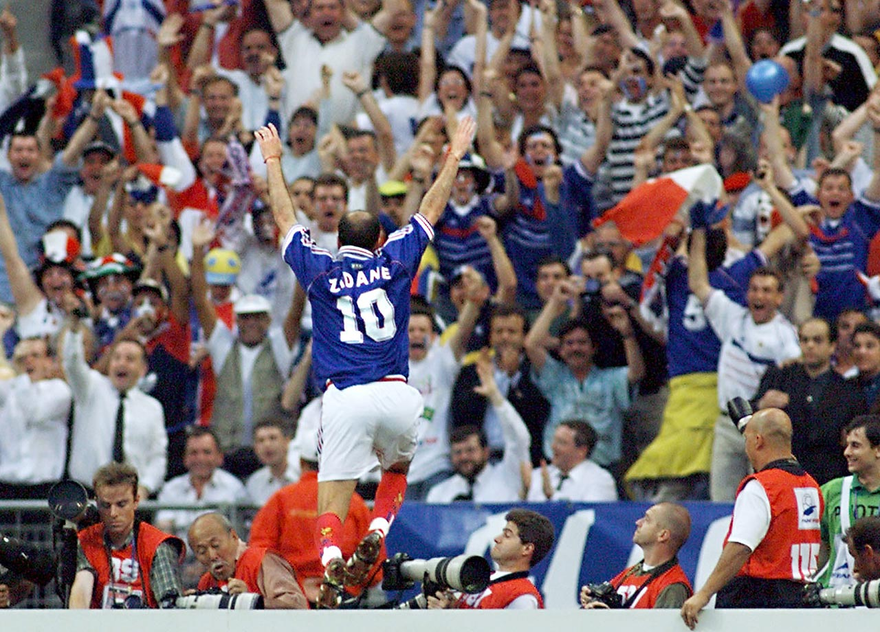 France's Zinedine Zidane jumps over the barrier as he celebrates his first goal during the 1998 World Cup final.