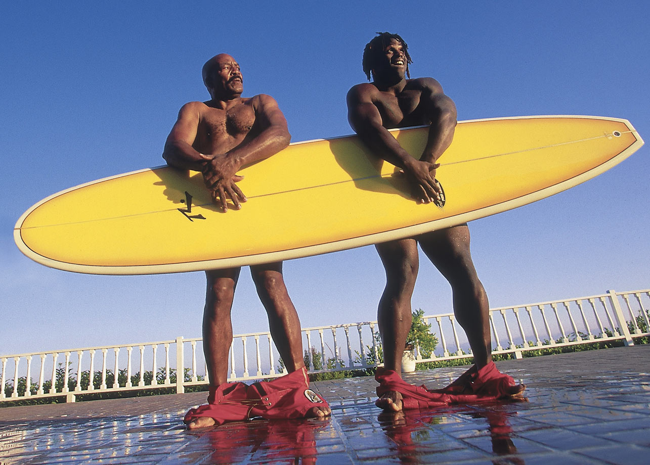 Jim Brown and then-New Orleans Saints running back Ricky Williams cover up behind a surfboard for a Sports Illustrated feature in 1999.