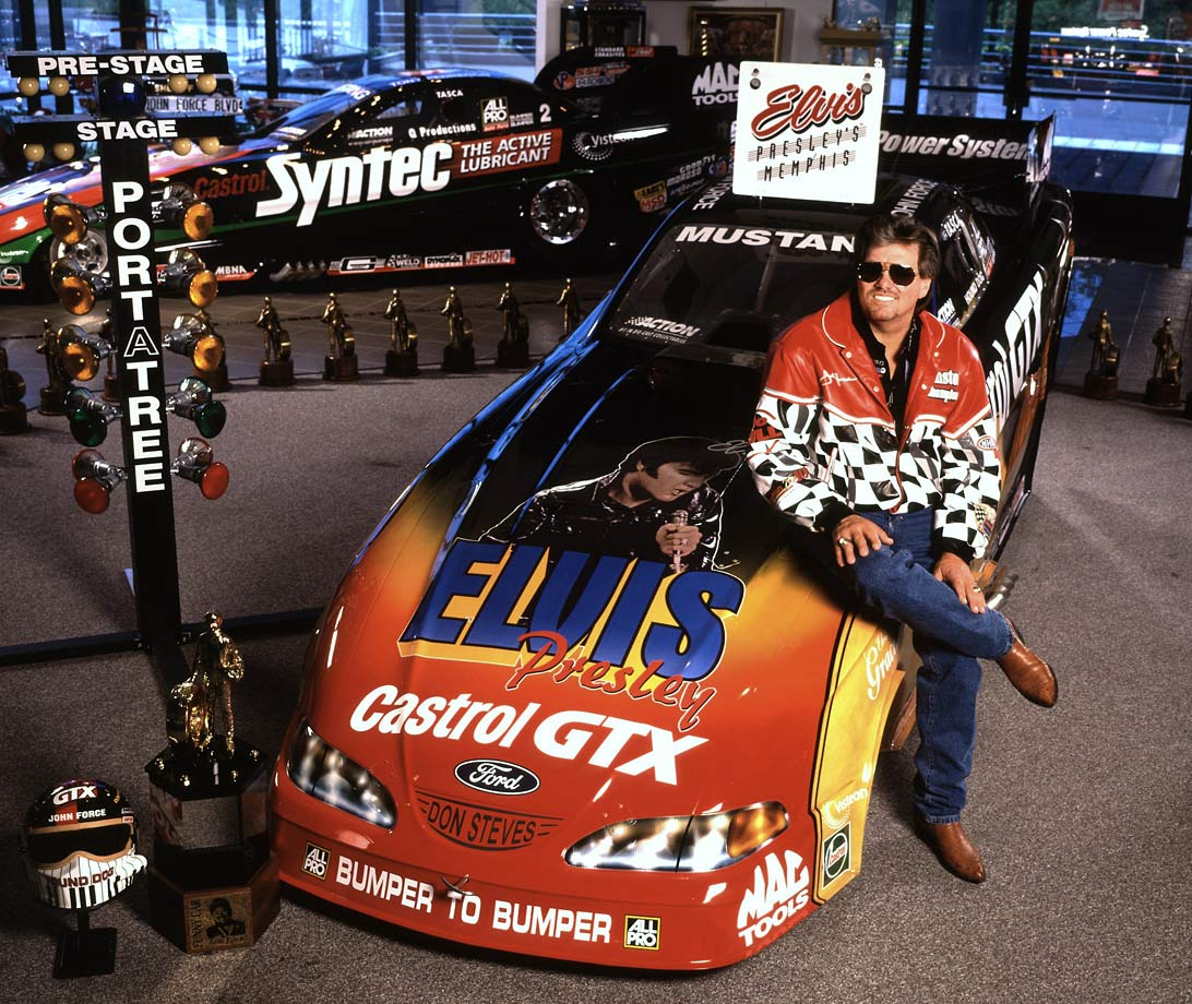 John Force poses with his Elvis Presley car in his garage on Aug. 30, 1999.
