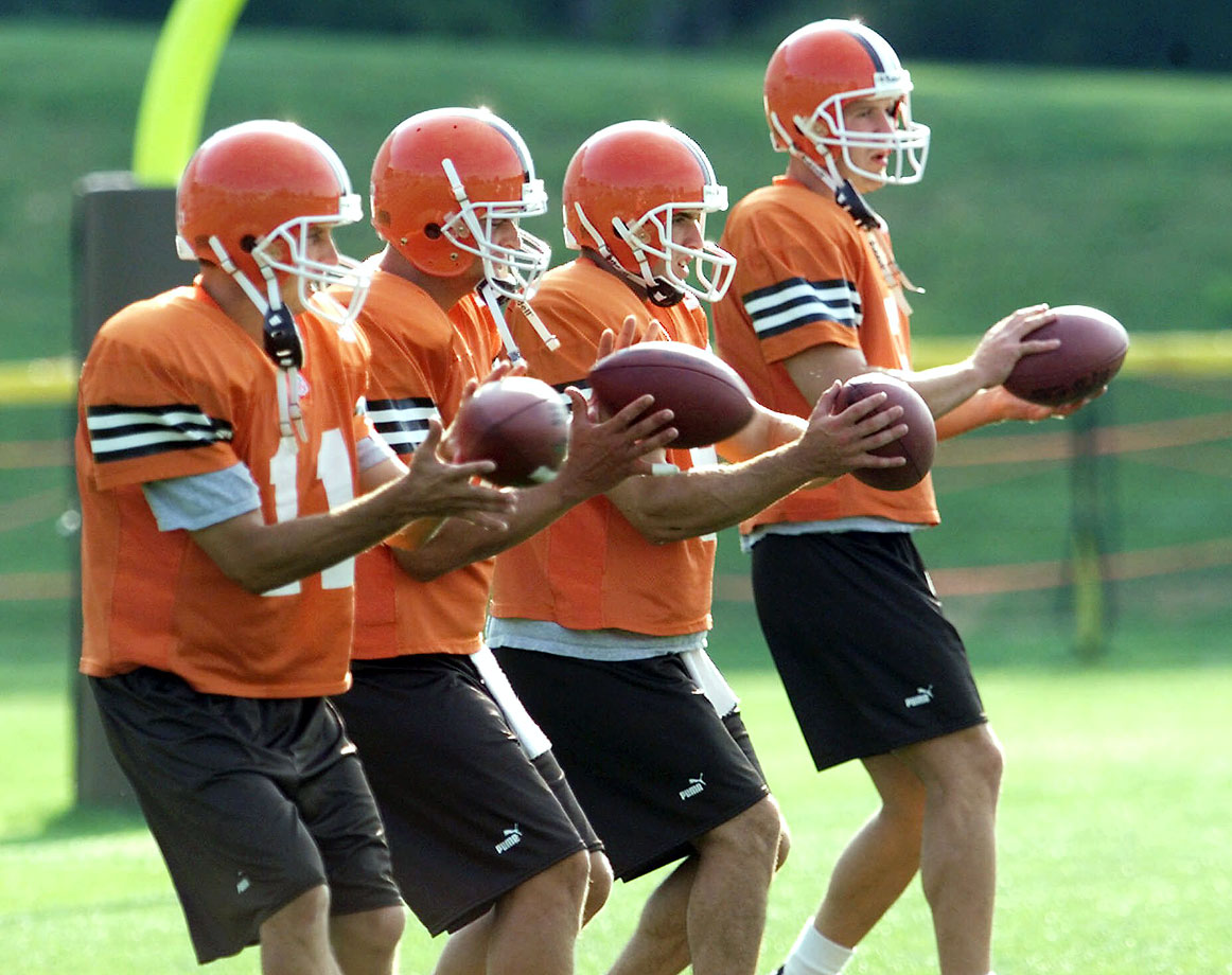 Quarterbacks Ty Detmer, Thad Busby, Mike Cook and Tim Couch practice taking snaps from the shotgun formation at the Browns training camp. This was Cleveland's first season of football since Art Modell moved the original franchise to Baltimore following the 1995 season.