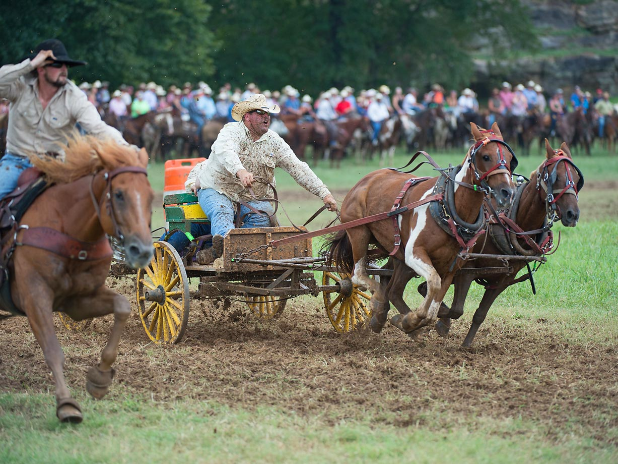 "Tater Wilbanks and Rickey Crabtrey, former Buckboard Champion from team ""Triple J"", follow behind their outrider (left side). The outrider must finish in front of the wagon for the team to qualify in the Buckboard division."