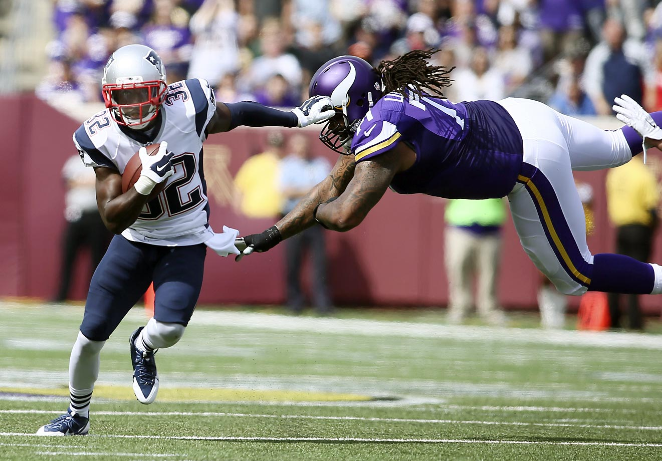 New England free safety Devin McCourty avoids Minnesota's Phil Loadholt during an interception.