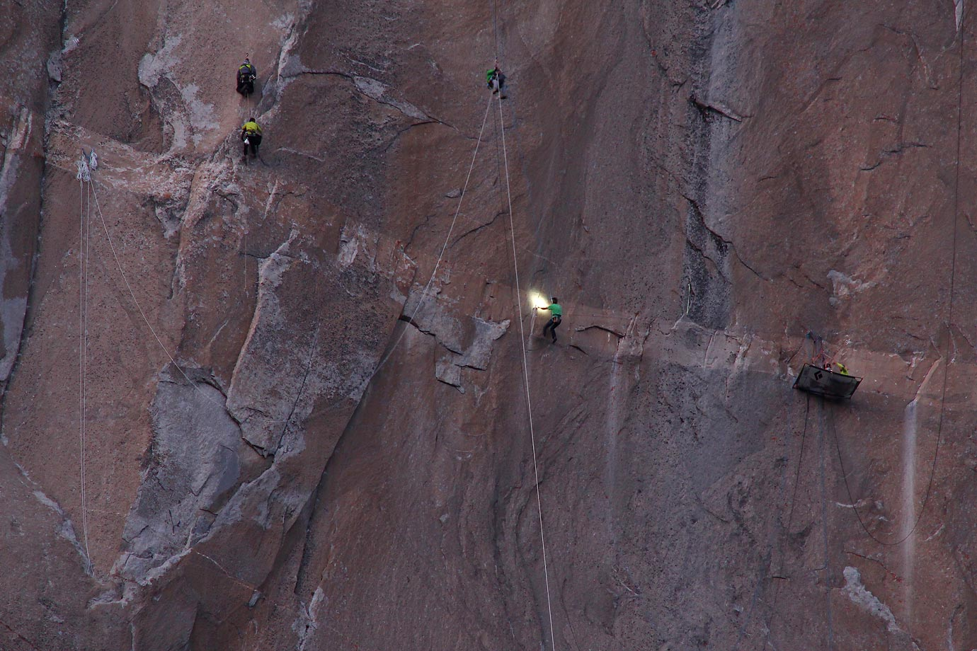 Kevin Jorgeson (center, in green) navigating Pitch 15 while Tommy Caldwell (right, in yellow) belays.  Multiple cameramen hang on ropes taking photos and video.