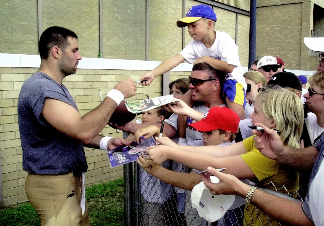 St. Louis quarterback Kurt Warner signs autographs following the Rams' practice during training camp at Western Illinois University in Macomb, Ill.