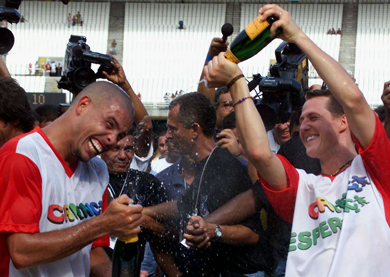 F1 racer Michael Schumacher of Germany douses Ronaldo with champagne after a friendly match for UNICEF in Rio de Janeiro in 2001.