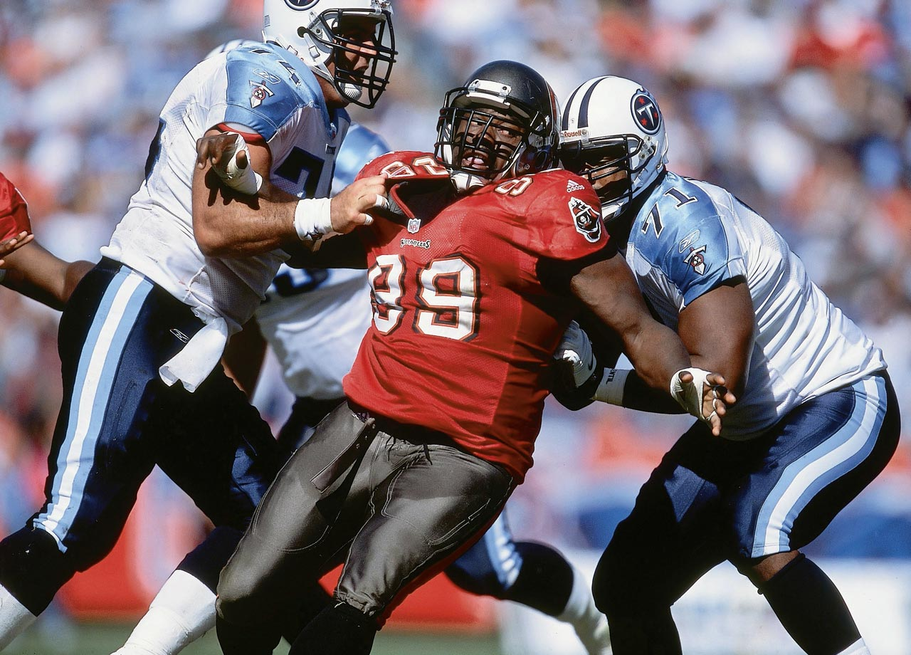 Warren Sapp is held by two linemen during the Tampa Bay Buccaneers game against the Tennessee Titans on Oct. 14, 2001 in Nashville, Tenn. The Bucs lost the game, 31-28 in OT.