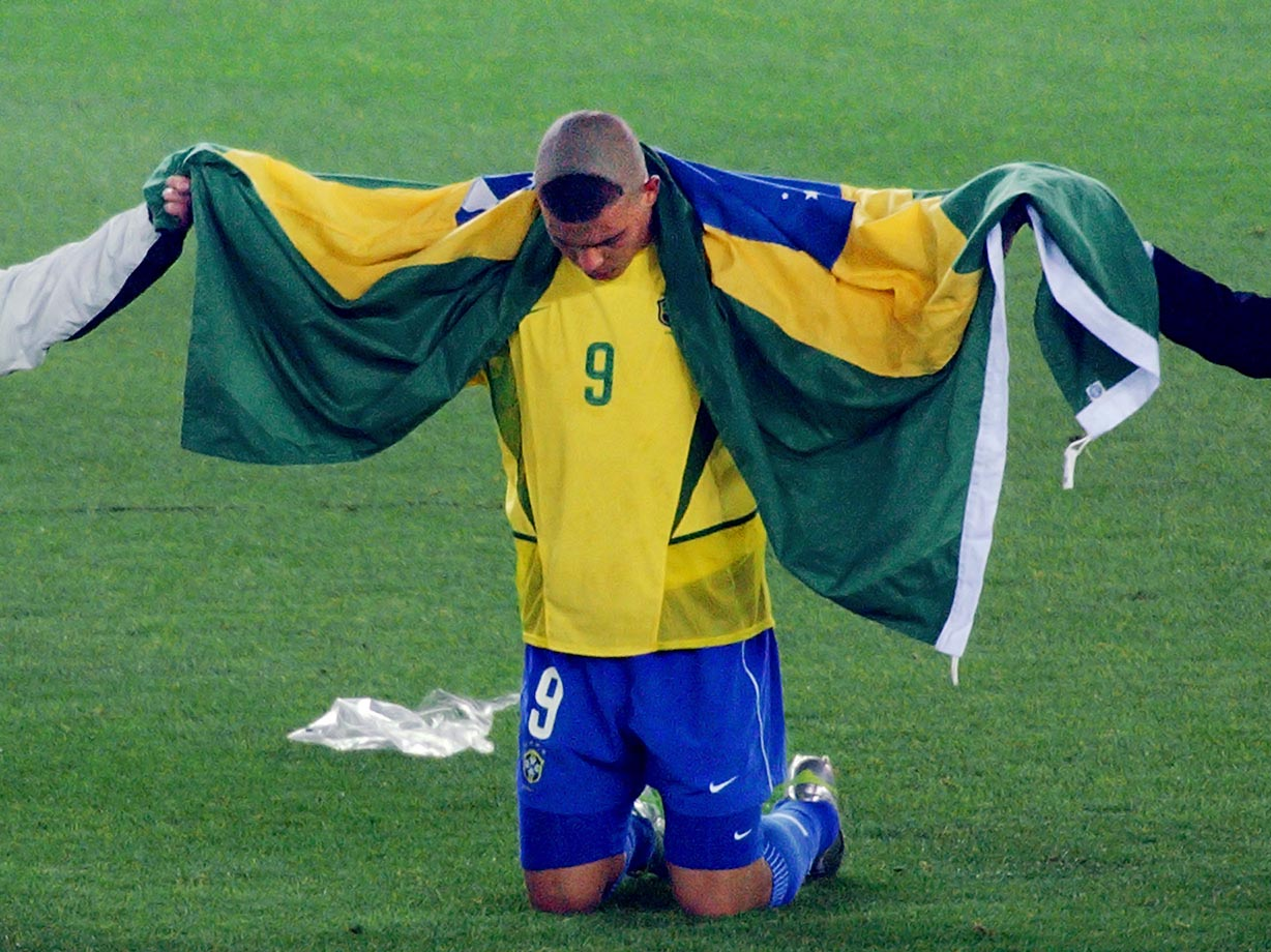 Ronaldo, sporting his famous triangle haircut, celebrates on the pitch after Brazil beat Germany 2-0 to win its fifth World Cup in 2002.