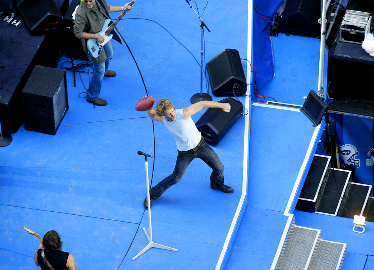 "Jon Bon Jovi looks to throw a football into the crowd while performing during ""NFL Kickoff Live from Times Square"" in New York City."