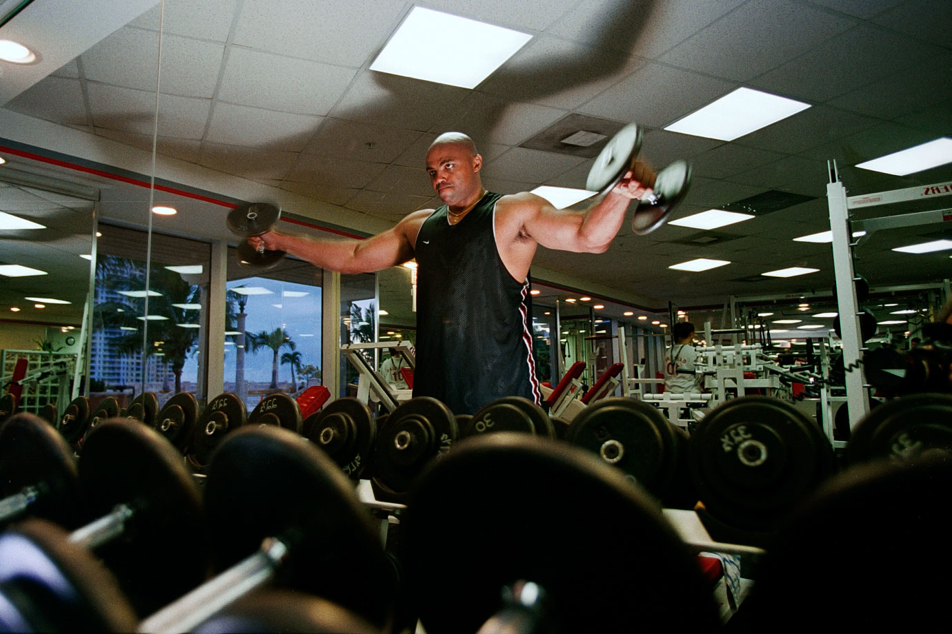Charles Barkley lifts weights in a gym.