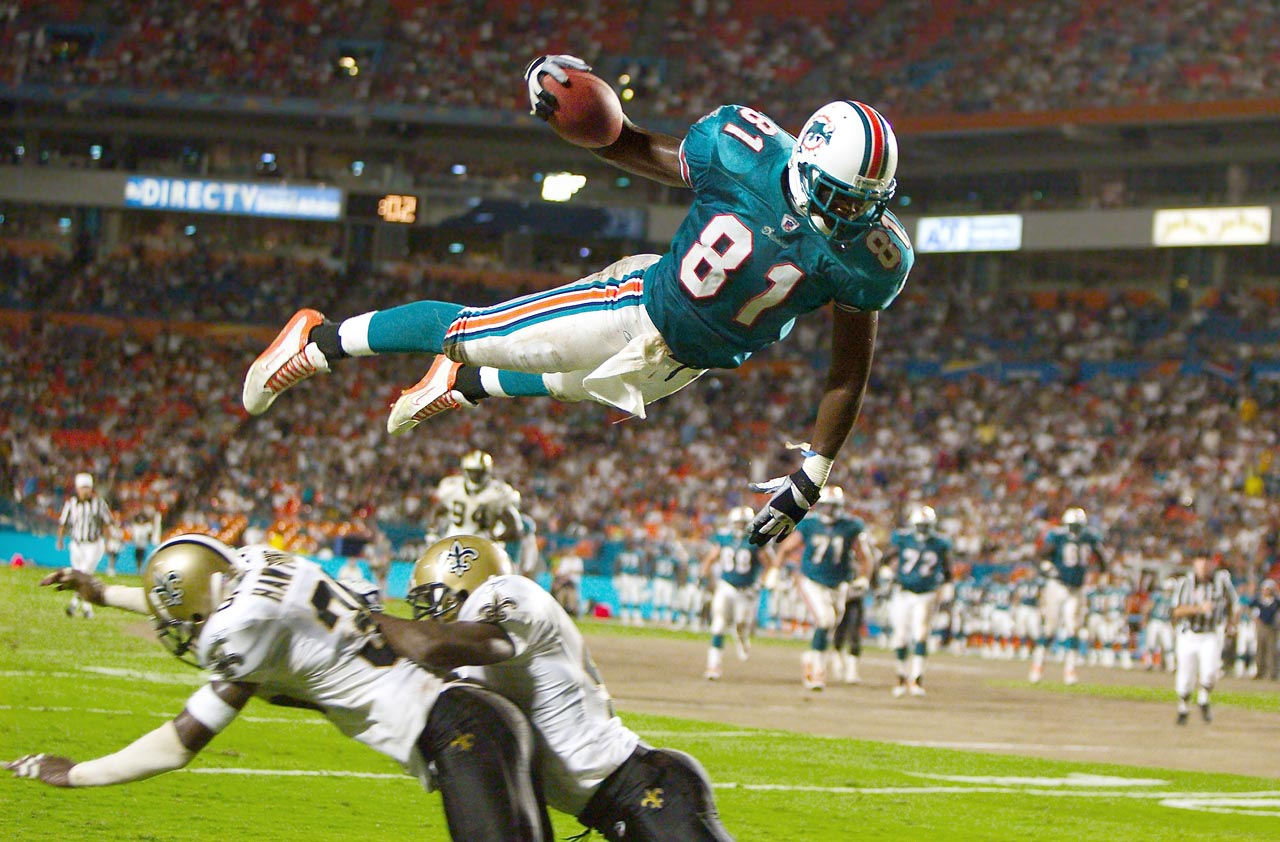 Dolphins tight end Randy McMichael soars over Saints defenders to score during a preseason game.
