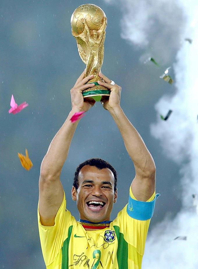Brazilian defender and team captain Cafu holds up the World Cup trophy triumphantly as confetti rains down on him.  Brazil defeated Germany, 2-0, in the final match of the 2002 World Cup.